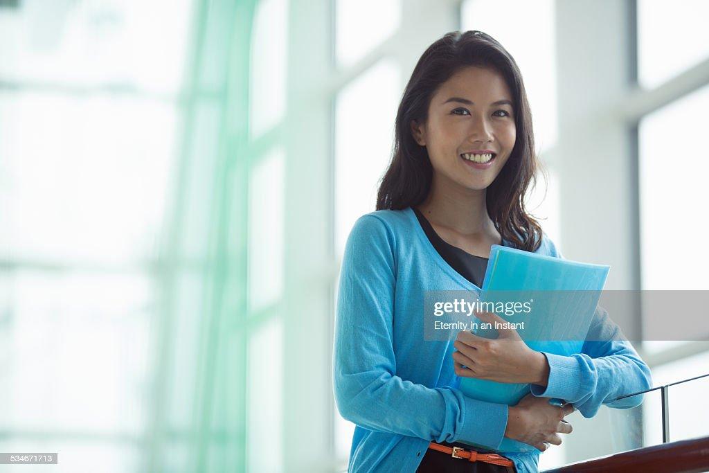 Woman holding folders next to a window : Stock Photo