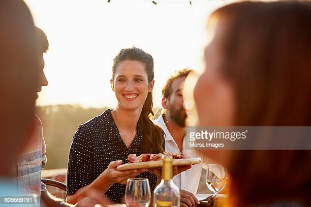 Woman holding food at dinner with friends