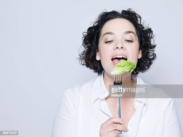 woman holding fork with leaf of salad - grasa nutriente fotografías e imágenes de stock