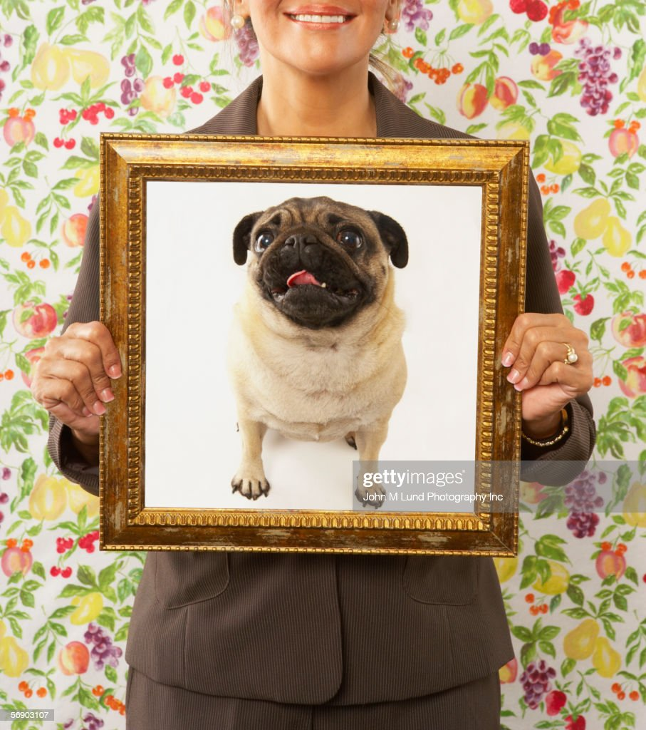 Woman holding framed picture of dog : Stock Photo