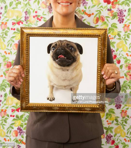 woman holding framed picture of dog - ugly asian woman stock photos and pictures