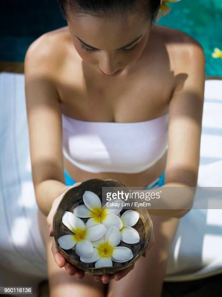 woman holding frangipani in container at poolside - off shoulder stock pictures, royalty-free photos & images