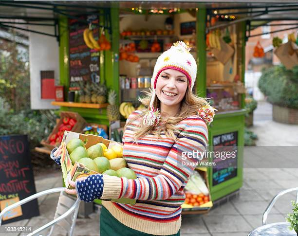 Woman holding fresh fruit in front of juice bar.