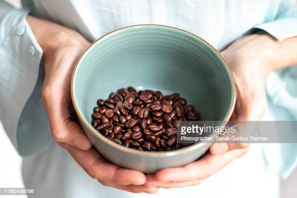 woman holding fresh roasted coffee beans in a green bowl - basak gurbuz derman stock photos and pictures