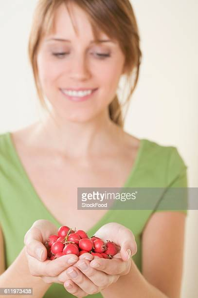 Woman holding fresh rose hips