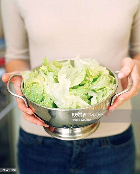 Woman holding freshly washed iceberg lettuce
