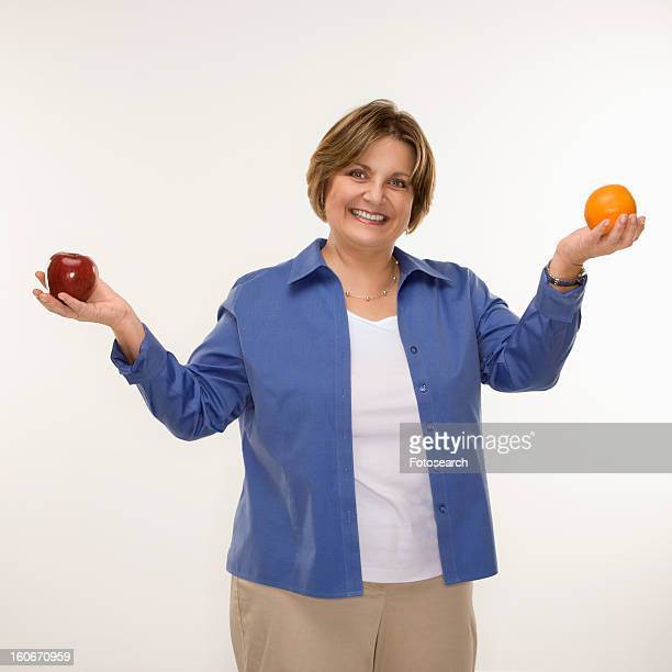 woman holding fruit in outstretched arms and smiling