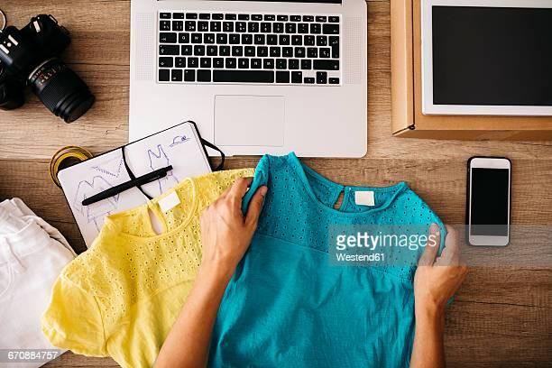 woman holding garment at desk - top garment stock-fotos und bilder