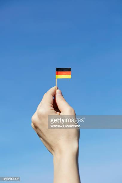 woman holding german flag in hand - german flag stock pictures, royalty-free photos & images