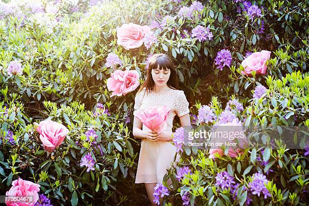 Woman holding giant rose, standing in flowerbush.