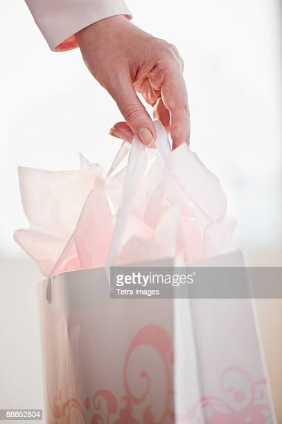 Woman holding gift bag, close-up