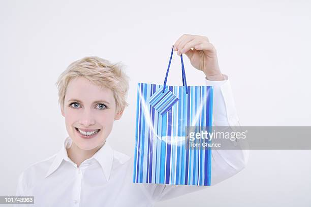 Woman holding gift bag, portrait