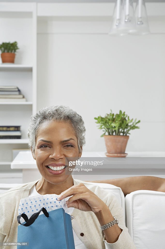 Woman holding gift, smiling, portrait : Stockfoto