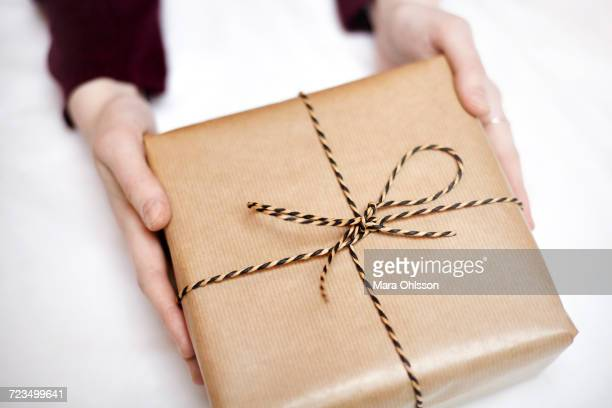 Woman holding gift wrapped in brown paper, decorated with string, close-up