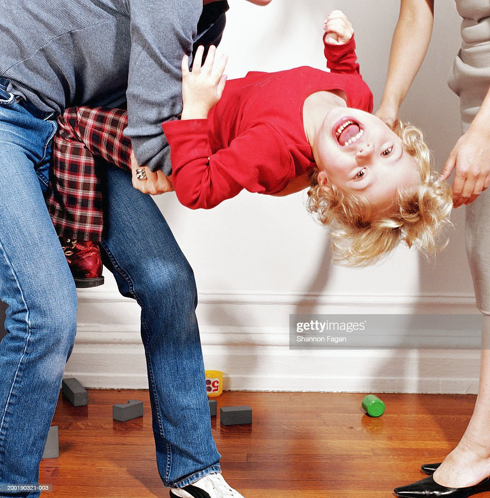Woman holding girl (2-4) having tantrum, low section : Stock Photo