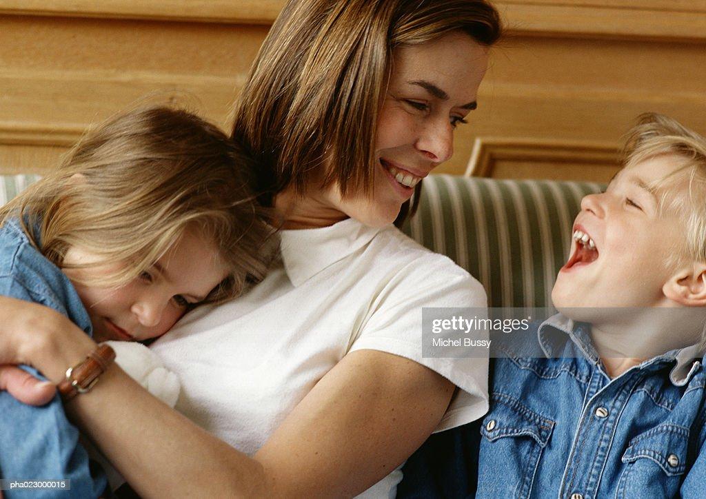 Woman holding girl in arms, looking at boy laughing : Stockfoto