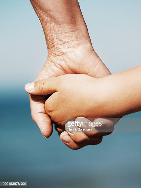 Woman holding girl's (5-7) hand, close up of hands