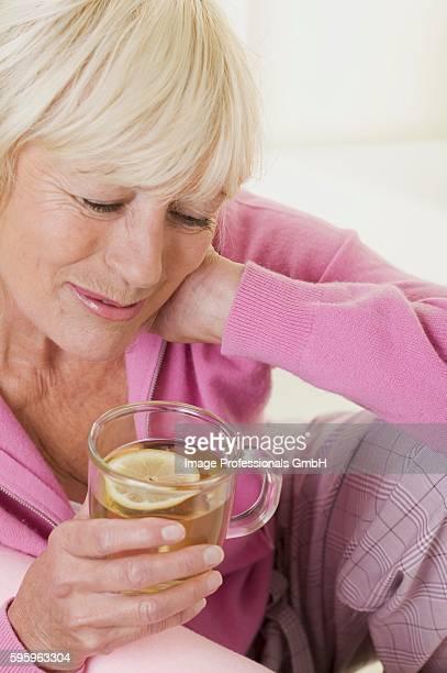 Woman holding glass cup of lemon tea
