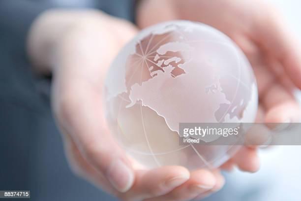 Woman holding glass globe, focos on globe