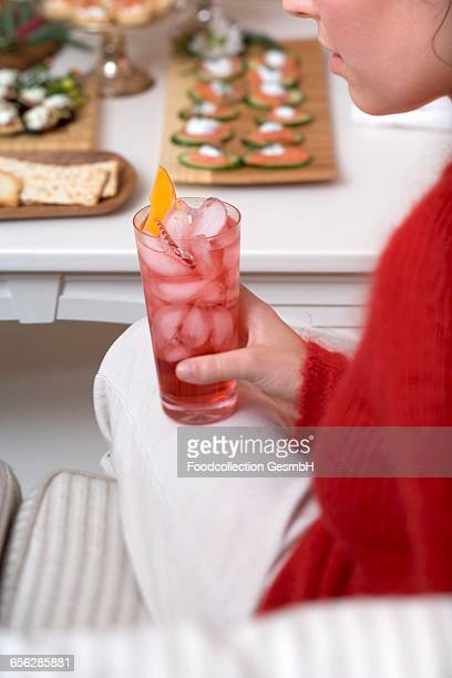 Woman holding glass of Campari with ice cubes, snacks in background