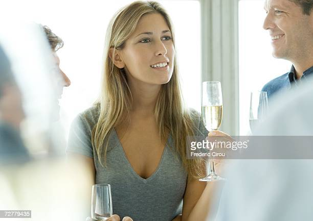 Woman holding glass of champagne during cocktail party