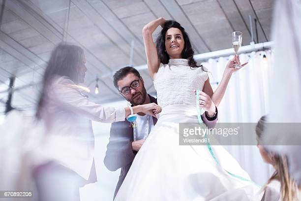 woman holding glass of champagne trying on wedding dress - wedding dress stock pictures, royalty-free photos & images