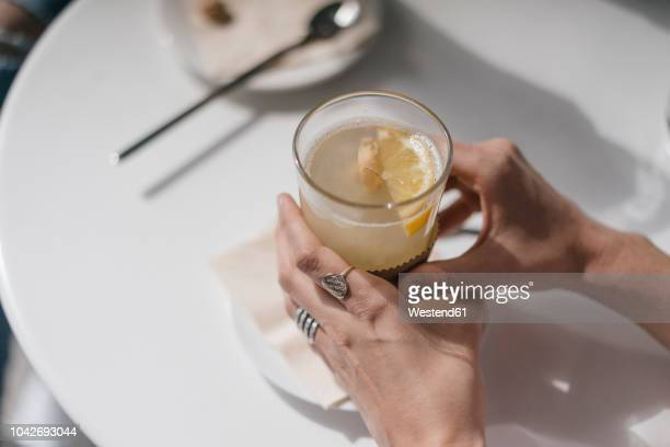 woman holding glass of ginger lemon tea - ginger spice stock pictures, royalty-free photos & images