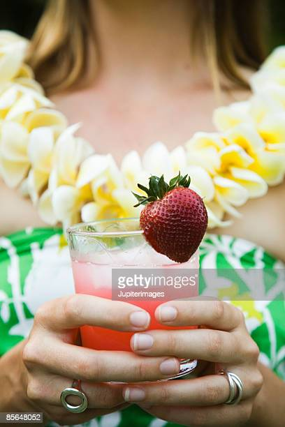 Woman holding glass of juice with strawberry