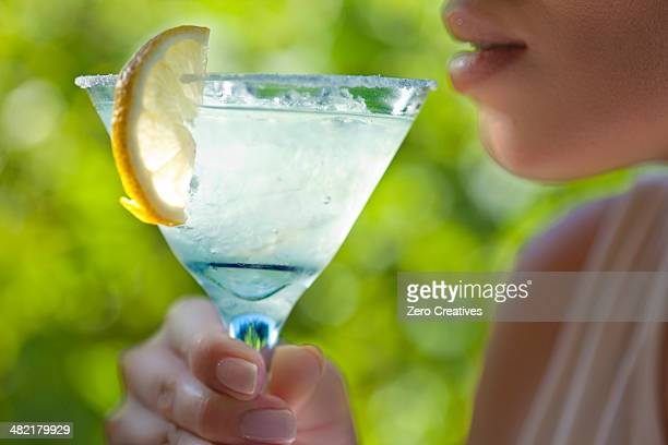 Woman holding glass of margarita to mouth