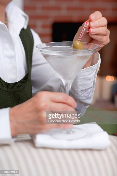 Woman holding glass of Martini with olive