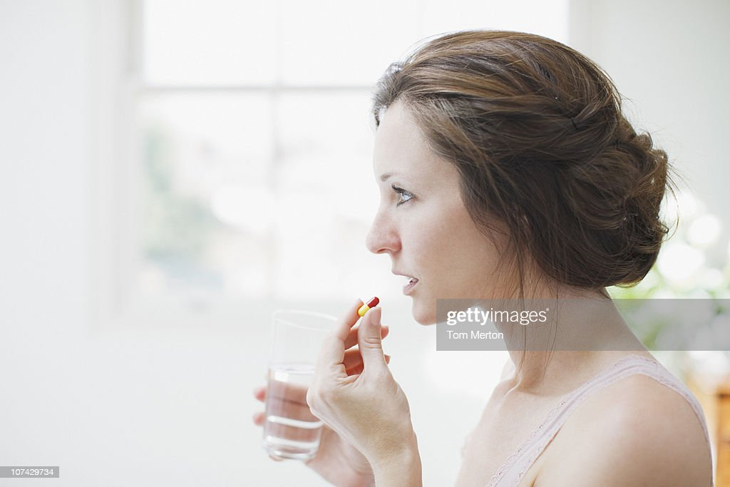 Woman holding glass of water and taking capsule : Stock Photo