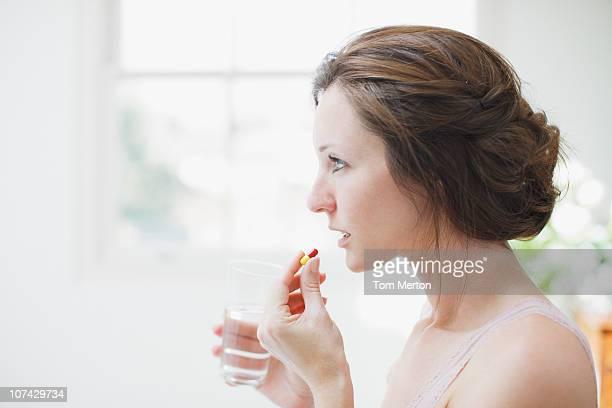 Mujer agarrando vaso de agua y tomar la cápsula