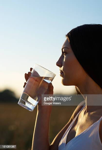Woman holding glass of water at sunset.