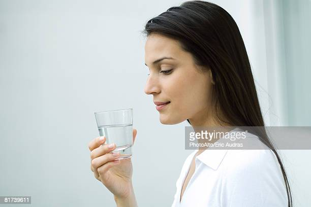 Woman holding glass of water, looking down, side view