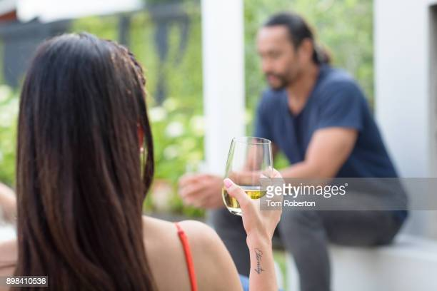 Woman holding glass of white wine in back yard