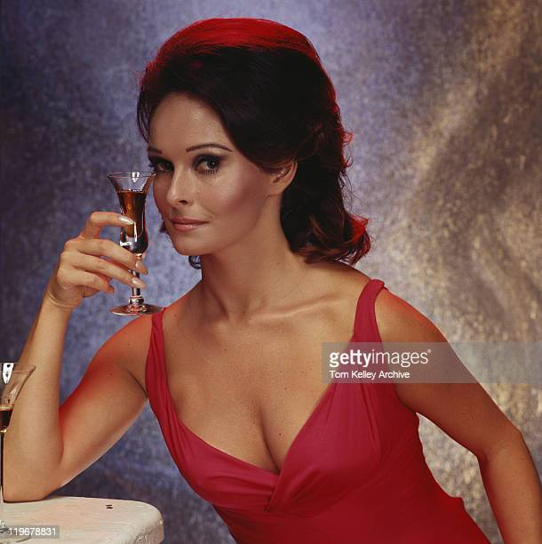Woman holding glass of wine, portrait, close-up