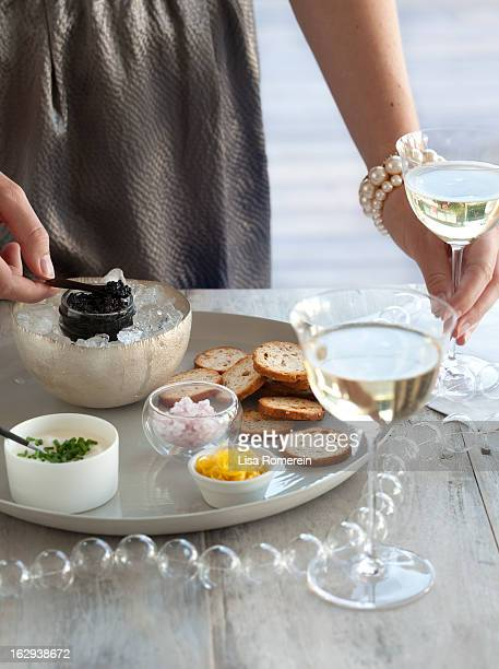 Woman holding glass of wine & serving caviar