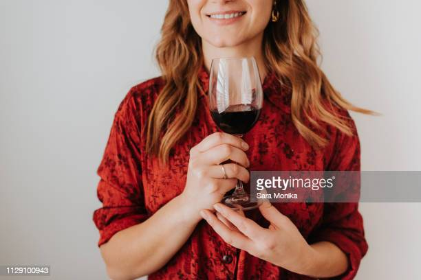 woman holding glass of wine, white background - red blouse stock pictures, royalty-free photos & images