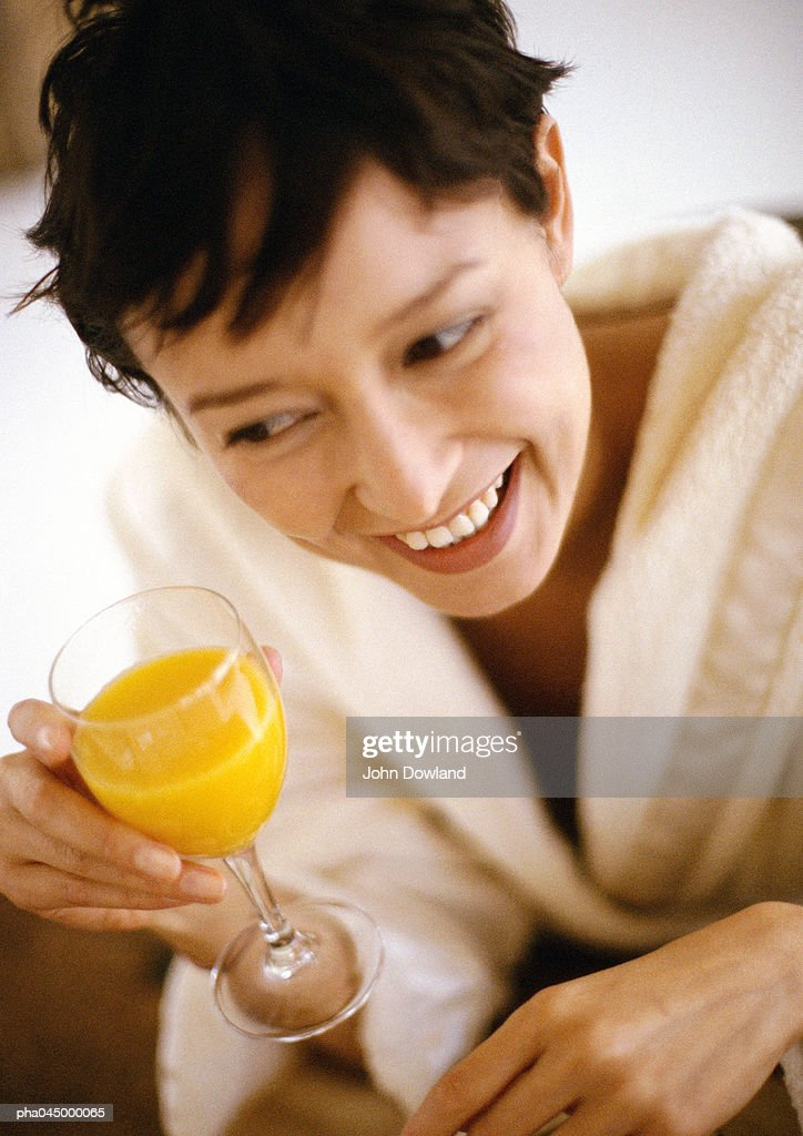 Woman holding glass, smiling, high angle view, close-up : Stockfoto
