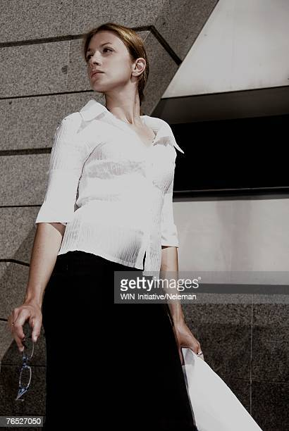 woman holding glasses and drawings, looking away - 女性建築家 ストックフォトと画像