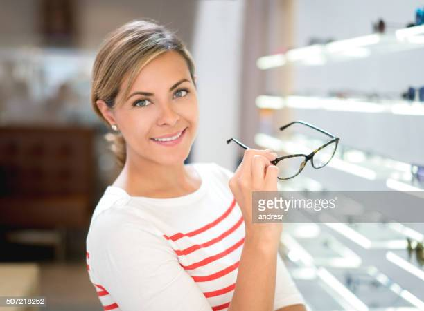 Woman holding glasses at the optician's shop