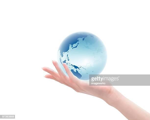 Woman holding globe against sky
