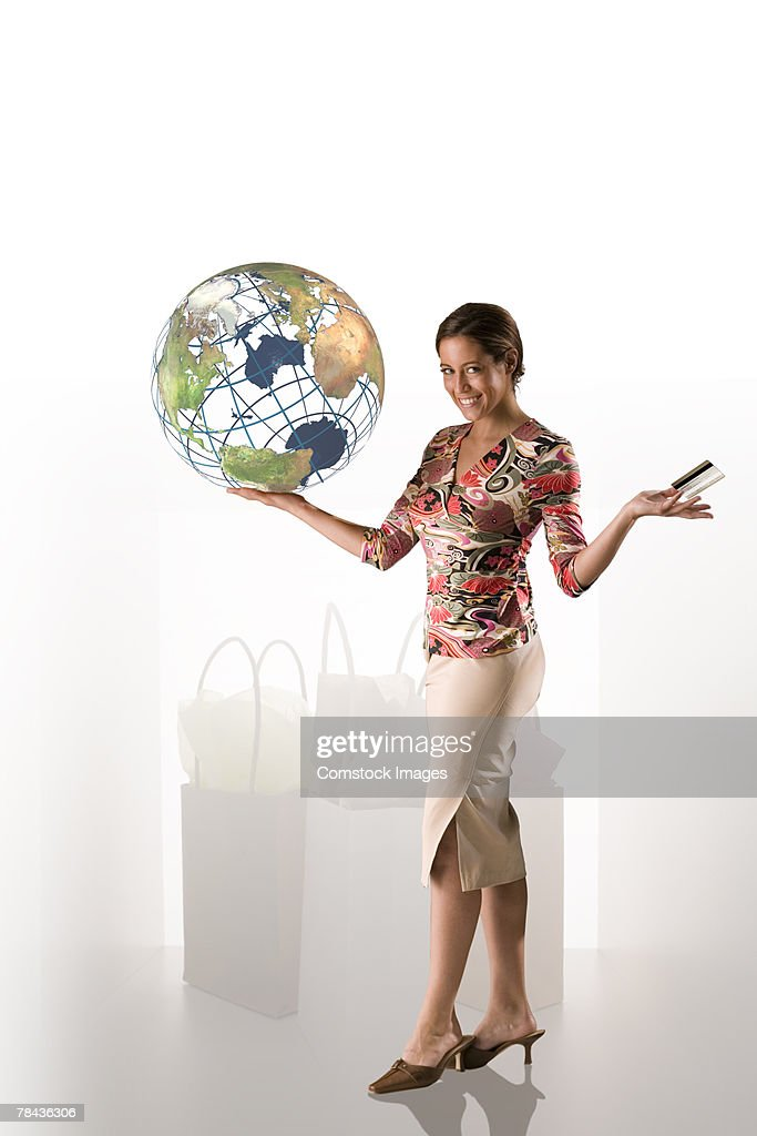 Woman holding globe and credit card : Stockfoto