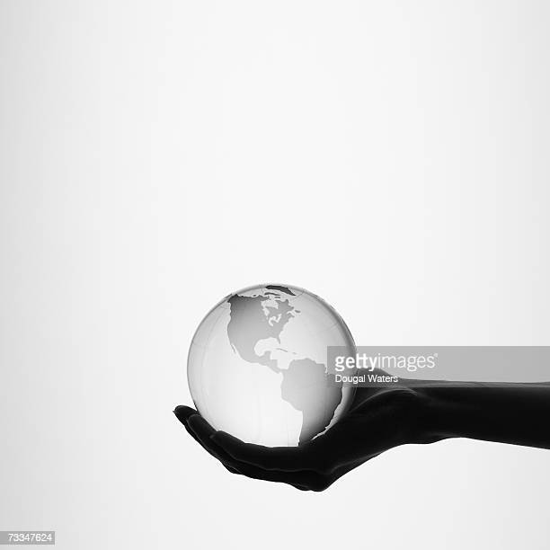 Woman holding globe, close-up hand