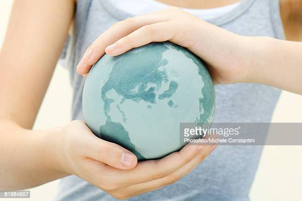 woman holding globe in cupped hands, close-up, cropped view - world kindness day fotografías e imágenes de stock