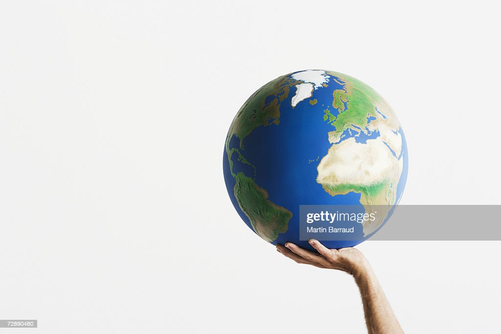 Woman holding globe in raised hands against white background, close-up : Stock Photo