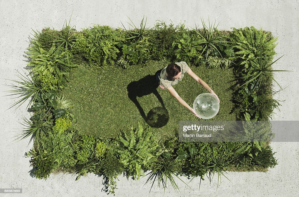 Woman holding globe on lush lawn in cement courtyard : Stock Photo