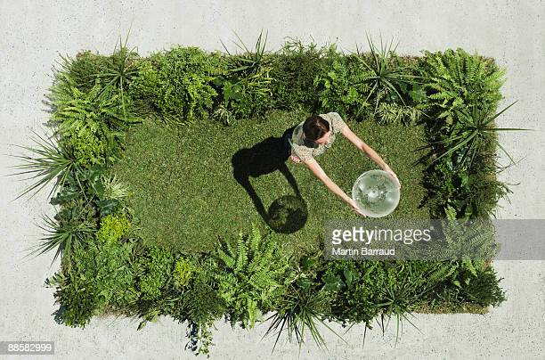 Woman holding globe on lush lawn in cement courtyard