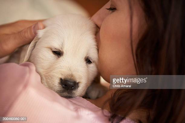 woman holding golden retriever puppy, view over shoulder, close-up - golden retriever photos et images de collection