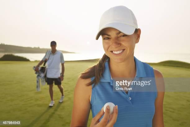 Frau holding Golfball auf dem Golfplatz